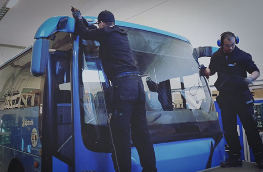 Two guys fixing the windshield on a bus