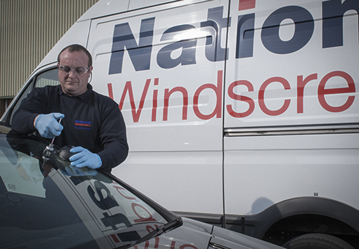 "Car with text ""National windscreens"" behond a guy fixing a cars windscreen"