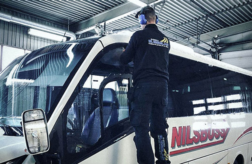 A guy fixing the windshield on a bus